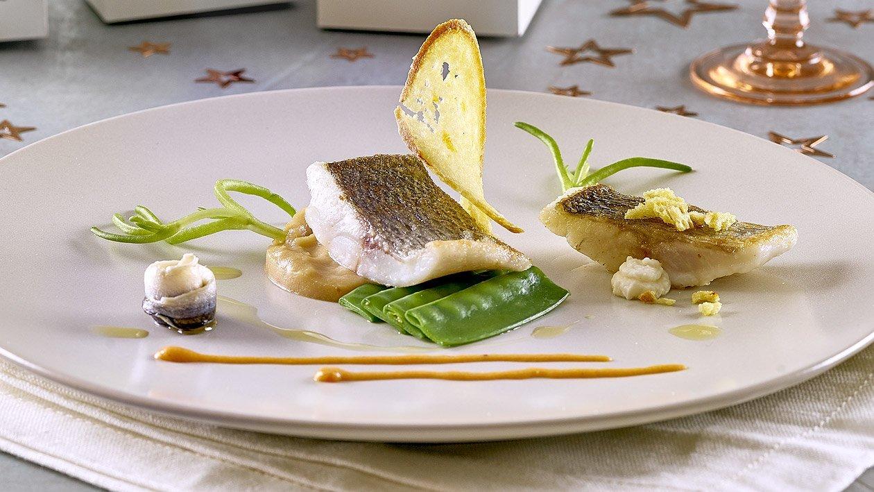 Gebratener Wolfsbarsch auf Bouillabaisse-Kartoffelpüree, Erbsenschotten, Rouille und eingelegeten Sardinen